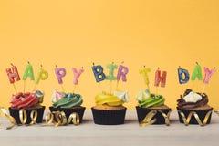Kleine Kuchen mit den Kerzen alles Gute zum Geburtstag des Wortes buchstabierend Lizenzfreies Stockfoto