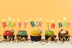 Kleine Kuchen mit den Kerzen alles Gute zum Geburtstag des Wortes buchstabierend lizenzfreie stockbilder