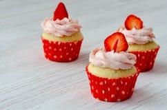 Kleine Kuchen mit Erdbeerdekoration auf einem weißen hölzernen Hintergrund lizenzfreie stockfotografie