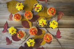 Kleine Kuchen mit orange und gelber Zuckerglasur auf altem rustikalem hölzernem Hintergrund lizenzfreie stockbilder