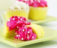 Kleine Kuchen mit rosafarbener Vereisung und einem Glas Milch Stockfoto