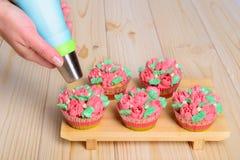 Kleine Kuchen mit Sahne auf hölzernem Hintergrund stockfotos