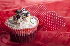 Kleine Kuchen und das Herzsymbol auf einem roten Hintergrund stockfotografie