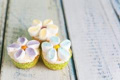 Kleine Kuchen verziert mit Buttercreme- und -eibischblumen stockbild