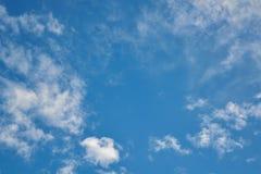 Kleine Kumulus- und Cirrus-Wolken laufen von der Mitte in den verschiedenen Richtungen auseinander lizenzfreie stockfotos