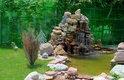 Kleine kunstmatige vijver met een fontein in de de zomertuin Het ontwerp van het landschap stock foto
