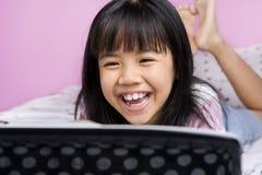 Kleine lachende Mädchen beim Überwachen des Laptops Stockfoto