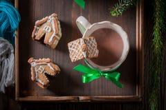 Kleine Lebkuchenhäuschen mit geschmackvollem Kakao am Weihnachtsabend Stockfotografie