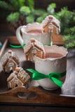 Kleine Lebkuchenhäuschen mit heißer Schokolade am Weihnachtswinterabend Lizenzfreies Stockfoto