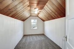 Kleine lege zolderruimte met het houten met panelen bekleden en gewelfd plafond Stock Afbeeldingen