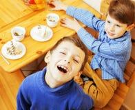Kleine leuke jongens die dessert op houten keuken eten Het binnenland van het huis glimlachende aanbiddelijke vriendschaps samen  Royalty-vrije Stock Foto
