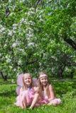 Kleine leuke meisjes in de tot bloei komende appeltuin Stock Foto