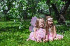 Kleine leuke meisjes in de tot bloei komende appeltuin Stock Foto's