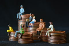 Kleine Leute, die auf Geld sitzen Lizenzfreies Stockfoto