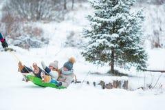 Kleine Mädchen, die das Rodeln am Wintertag genießen Vater, der seine kleinen entzückenden Töchter rodelt Familienurlaub an Lizenzfreie Stockfotos