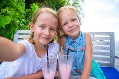 Kleine Mädchen, die das selfie und Trinken geschmackvoll nehmen lizenzfreie stockbilder