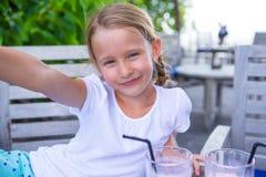 Kleine Mädchen, die das selfie und Trinken geschmackvoll nehmen stockfoto