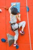 Kleine Mädchen, die eine künstliche Wand im Freien mit Orange im Park im Freien klettern Stockfotos