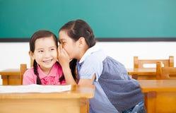 Kleine Mädchen, die Geheimnis flüstern und teilen Stockbild