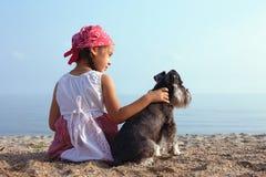 Kleine Mädchen, die ihren Hund umfassen Stockfotos