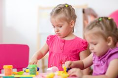 Kleine Mädchen, die lernen, bunten Spielteig zu bearbeiten Lizenzfreie Stockbilder