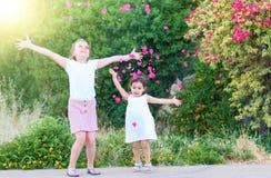 Kleine Mädchen, die oben rosa Blumenblätter werfen lizenzfreies stockfoto