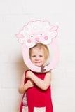 Kleine Mädchen, die Schafmaske auf weißem Hintergrund halten Stockfotografie