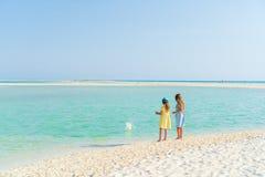Kleine Mädchen, die Spaß am tropischen Strand zusammen spielt auf der Küste haben Stockbild