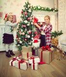 Kleine Mädchen, die Weihnachtsbaum verzieren und Geschenke vorbereiten stockfotografie