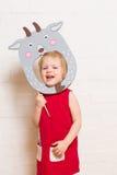 Kleine Mädchen, die Ziegenmaske auf weißem Hintergrund halten Lizenzfreies Stockbild
