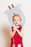 Kleine Mädchen, die Ziegenmaske auf weißem Hintergrund halten Lizenzfreies Stockfoto
