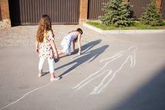 Kleine Mädchen, die zusammen draußen zu Hause an einem Sommertag spielen lizenzfreie stockfotos