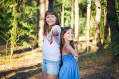 Kleine Mädchen, die zusammen draußen zu Hause an einem Sommertag spielen Lizenzfreies Stockbild