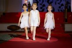 Kleine Mädchen gehen auf Podium während der KinderModeschau Lizenzfreie Stockfotografie