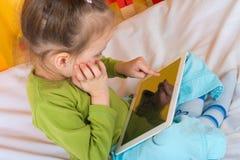 Kleine Mädchen mit Tablette stockfoto