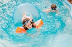 Kleine Mädchen schwimmt im Pool bis zum einem Sommertag Lizenzfreie Stockfotos