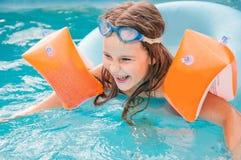 Kleine Mädchen schwimmt im Pool bis zum einem Sommertag lizenzfreie stockbilder
