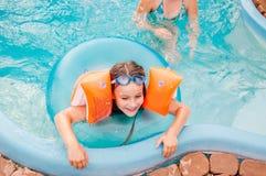 Kleine Mädchen schwimmt im Pool bis zum einem Sommertag Stockfotos