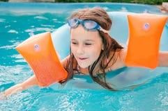 Kleine Mädchen schwimmt im Pool bis zum einem Sommertag Stockfoto