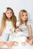 Kleine Mädchen und ein Baby im weißen Kleidungssitzen Lizenzfreies Stockbild