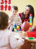Kleine Mädchen und weiblicher Lehrer im Kindergarten lizenzfreies stockfoto