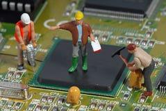 Kleine Männer, die einen Computer reparieren Stockbild