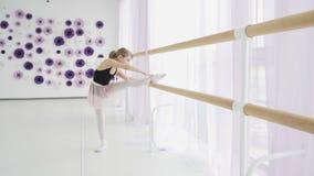 Kleine M?dchen unter Verwendung Ballett Barre, wenn das Bein getan wird, das ?bungen im Tanzstudio ausdehnt stock footage