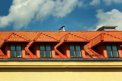 Kleine Mansardenfenster in einem roten mit Ziegeln gedeckten Dach gegen Hintergrund des blauen Himmels Stockbilder