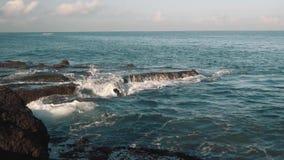 Kleine Meereswogen, die gegen dunkle Felsen sich waschen und spritzen stock video