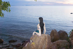 Kleine Meerjungfrau sitzt auf einer Klippe im Sonnenuntergang Lizenzfreie Stockfotos