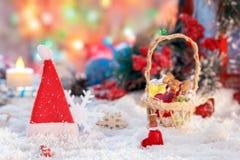Kleine mehrfarbige Glasflaschen von Sankt in einem Weidenkorb mit Geschenken auf dem Hintergrund eines roten Dekors der Laterne u Stockbild