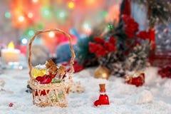 Kleine mehrfarbige Glasflaschen von Sankt in einem Weidenkorb mit Geschenken auf dem Hintergrund eines roten Dekors der Laterne u Stockbilder