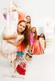 Kleine meisjes tijdens het winkelen tribune achter hangers Stock Foto's
