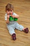Kleine meisjeszitting op houten vloer en spel met speelgoed Royalty-vrije Stock Afbeeldingen
